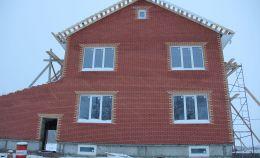 Фронтальная сторона кирпичного дома с остеклением