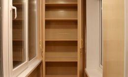 Шкаф для хранения из дерева на балконе с теплым остеклением