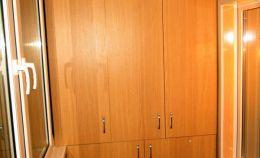 Большой шкаф из дерева на лоджии с теплым остеклением
