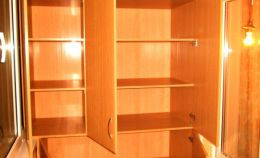 Большой деревянный шкаф с открытыми дверцами на лоджии